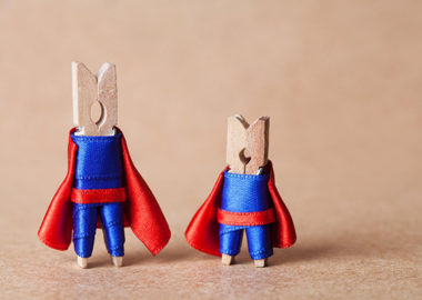 Two clothespins, dressed as superheros with red capes.