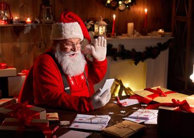 Santa waving at his phone for a virtual holiday celebration