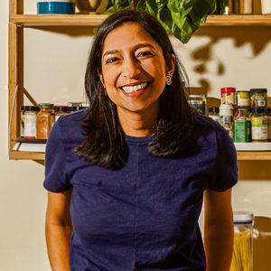 Priya Krishna in front of kitchen shelves