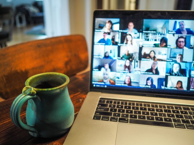 Laptop computer with Zoom call opened on screen and teal coffee mug